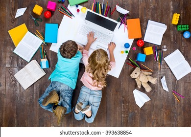 Happy children. Top view creative photo of little boy and girl on vintage brown wooden floor. Children lying near books and toys, and using laptop