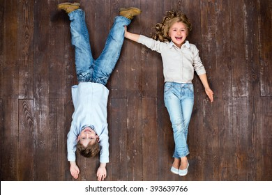 Happy children. Top view creative photo of little boy and girl on vintage brown wooden floor. Girl holding boy's leg. Boy is upside down
