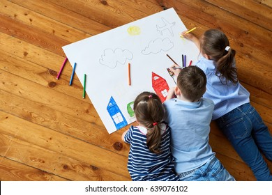 Happy children. Top view creative photo of little boy and girl on brown wooden floor. children draw together on a large sheet of paper