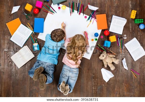 Joyeux enfants. Vue de dessus photo créative de petit garçon et fille sur un parquet marron vintage. Enfants allongés près des livres et des jouets et peignant