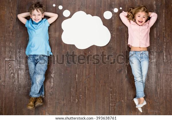 Niños felices. Foto creativa de la parte superior del suelo de madera marrón vintage. Niños tendidos cerca de nubes vacías con pensamientos, mirando cámara y sonriendo