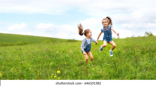 happy children twins sisters jumping and laughing on the meadow in summer
