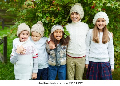 Happy children of various ages posing outdoors embracing and smiling to camera standing under lush green bush enjoying warm autumn day, all dressed in similar knit clothes