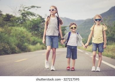 Happy children  walking on the road at the day time.  Concept of friendly family.