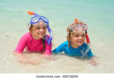 Happy children wearing snorkeling gear  on the beach
