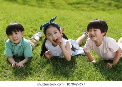 The happy children were playing on the grass