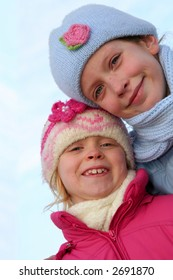 Happy children in winter outfit  on a blue sky background.