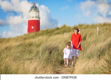 Happy children, young active boy and his adorable curly baby sister wearing a dress playing with sand toys on a sunny windy beach with a red lighthouse on Texel island, Holland, Netherlands