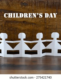 Happy Childrens Day concept with paper dolls on dark wood background.