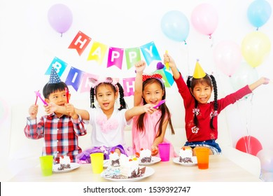 Happy children's party : Group of Asian boys and girls were having a fun birthday party. The four children sat down to eat cakes and nectar.