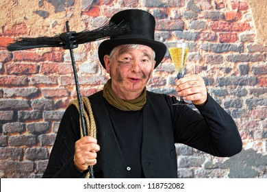 Happy chimney sweep toasting to the new year with a glass of champagne