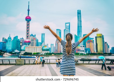 Happy China travel tourist success woman with arms up with Shanghai skyline on The Bund. Chinese girl winning. Happiness healthy living people in modern city. Woman winning goal challenge.