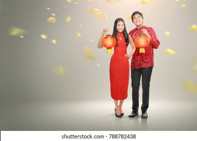 Happy chinese couple in cheongsam clothes holding red lanterns with confetti background. Happy Chinese New Year