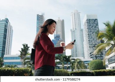 Happy Chinese female manager messaging on cell phone, drinking coffee. Successful Asian businesswoman walking to office in the morning, busy lady sending text with mobile telephone and going to work
