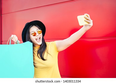 Happy Chinese girl making selfie with mobile smartphone outdoor - Asian social influencer woman having fun doing shopping - Concept of new generation youth lifestyle people and technology