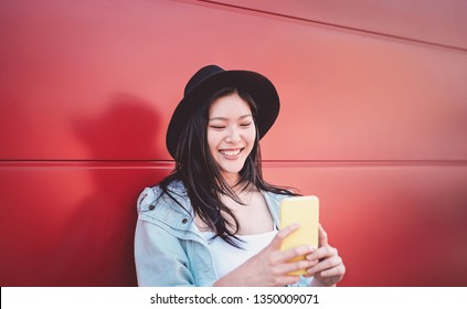 Happy Chinese girl using mobile phone outdoor - Asian social influencer woman having fun with new trends smartphone apps - Generation z, media, technology and youth millennial people lifestyle