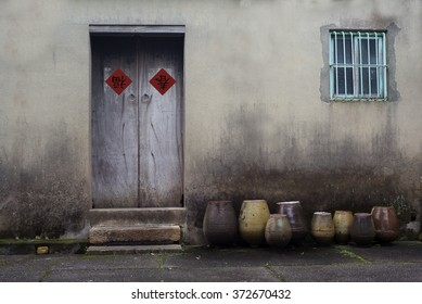 Happy Chinese lunar year . An old wooden door on grunge cement wall with Chinese lunar new year decoration and some urns in front of the wall.  The two Chinese character meaning good fortune.