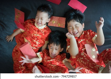 Happy chinese new year. 3 cute asian little boys are playing red envelopes together on the bed.