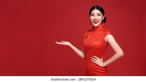 Happy Chinese new year. Asian woman wearing traditional cheongsam qipao dress with gesture of introduce isolated on red background.