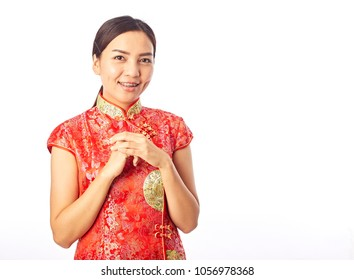 Happy Chinese New Year Portrait of Asian Chinese girl blessing, in traditional red qipao standing on plain background.