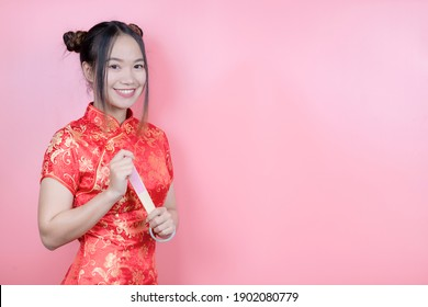 Happy Chinese New Year. Portrait beautiful Asian women in red color Chinese dress cheongsam with gestures of congratulations and look at camera isolated on pink background.
