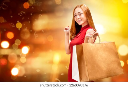 Happy chinese woman with cheongsam dress holding shopping bags. Happy Chinese New Year