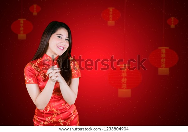 Happy Chinese woman wearing cheongsam dress while standing with congratulating gesture in red background