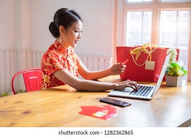 Happy chinese woman wearing a qipao dress traditional and buying online with a red credit card. Online Shopping Website on Laptop.