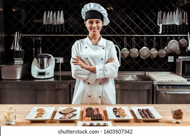 happy chocolatier in chef hat standing with crossed arms near tasty chocolate candies on plates