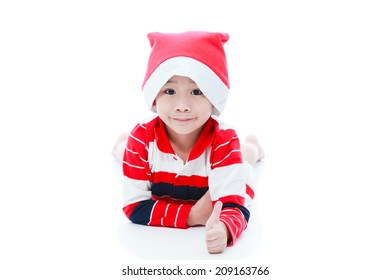 Happy christmas boy laying and smiling in santa hat showing thumbs up ,on white background