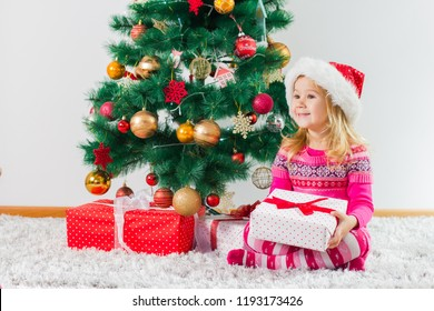 Happy Christmas Child With Gift Box And New Year Tree At Home.