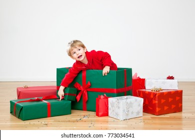 Happy Christmas  Cute Toddler Series with Gifts and Tree in his Modern Home with wooden floor and white walls