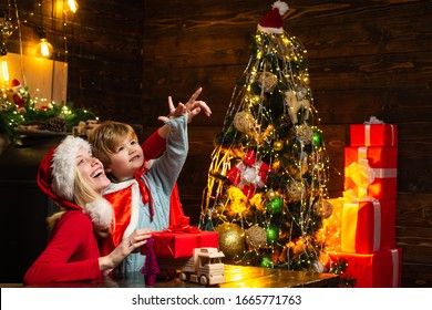 Happy Christmas family. Child and mother point out, shows your product. Happy mother is playing with her son. Family concept