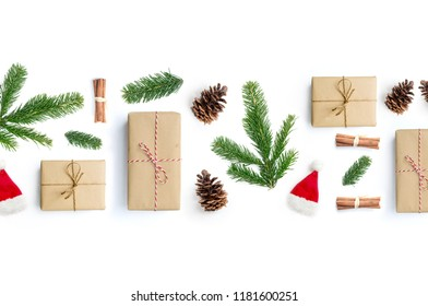 Happy Christmas layout composition, top view with xmas presents, cinnamon sticks, fir tree branches and pine cones on a white background.