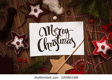 Happy Christmas lettering inscription on paper on wooden background with handmade toys.