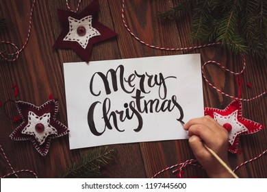 Happy Christmas lettering on a white sheet of paper on a wooden background, with handmade Christmas toys made of felt and fir branches. Top view, close-up and rustic style concept.