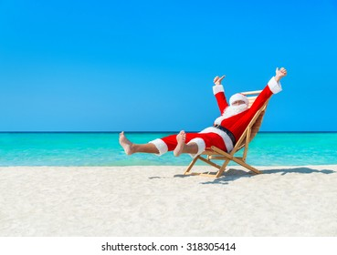 Happy Christmas Santa Claus on sunlounger at ocean sandy tropical beach - xmas travel vacation in hot countries concept