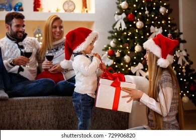Happy Christmas - Smiling kids opening Christmas present