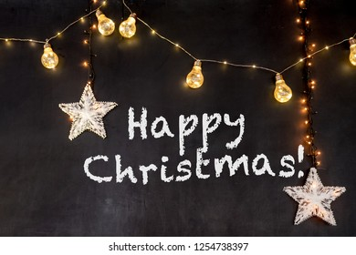 Happy Christmas text in black background with yellow lamps and stars