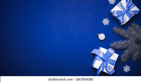 Happy Christmas. White gift with cyan bow, blue balls and winter tree in xmas decoration on azure background for greeting card. Christmas, winter, new year concept.