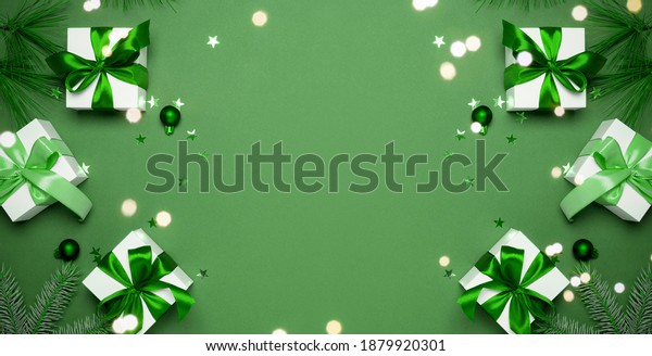 Happy Christmas. White gifts with emerald color bow, green balls and sparkling lights in xmas decoration on greenish background for greeting card. Christmas, winter, new year concept.