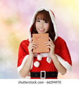 Happy Christmas woman holding gift box over colorful background.