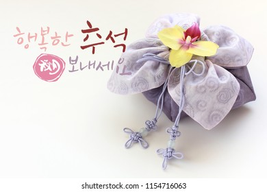 'Happy Chuseok &Hangawi, Translation of Korean Text : Happy Korean Thanksgiving Day' calligraphy and Korean traditional bag &knot of white background.