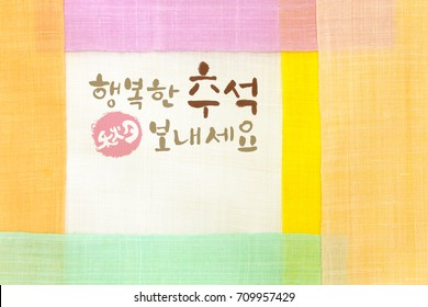 'Happy Chuseok & Hangawi, Translation of Korean Text : Happy Korean Thanksgiving Day' calligraphy and Korean traditional patchwork background of ramie fabric.
