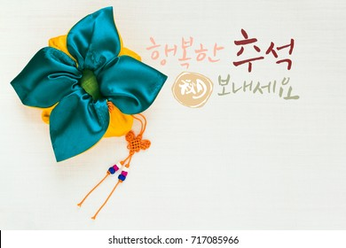 'Happy Chuseok & Hangawi, Translation of Korean Text : Happy Korean Thanksgiving Day' calligraphy and Korean traditional bag & knot background of white ramie fabric.