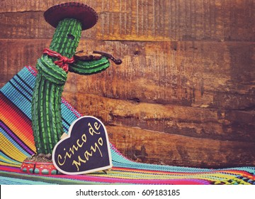 Happy Cinco de Mayo, 5th May, party celebration with with fun Mexican cactus and blackboard sign with text against a dark retro wood background, with applied retro style filter.