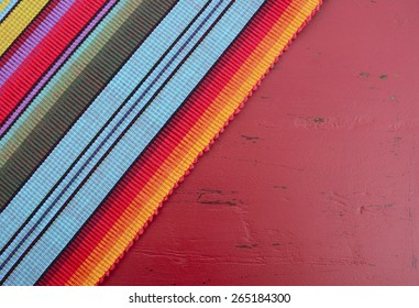 Happy Cinco de Mayo background with Mexican style fabric on distressed red wood table.