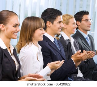 Happy clapping businesspeople at presentation, meeting, seminar or conference