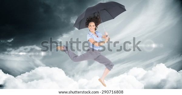 Happy classy businesswoman jumping while holding umbrella against blue sky