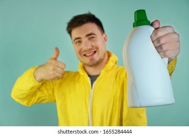 Happy Cleaner In A Yellow Suit Holds A Bottle Of Cleaning Product And Shows Thumb Up On A Blue Background